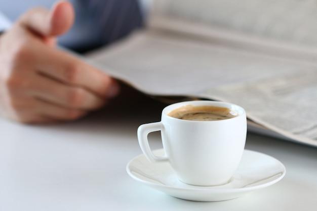 Taza de café de la mañana en la mesa de trabajo con analista de negocios en manos y leer el periódico