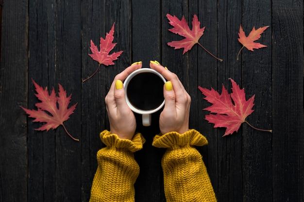 Taza de café en una mano femenina. fondo de madera, hojas de otoño. vista superior