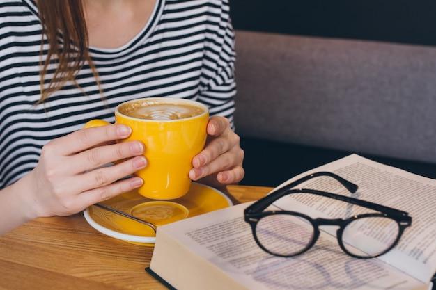 Taza de café en las manos de la niña
