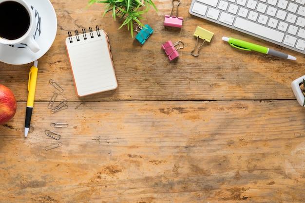 Taza de café; manzana; teclado y papelería de oficina en mesa de madera.
