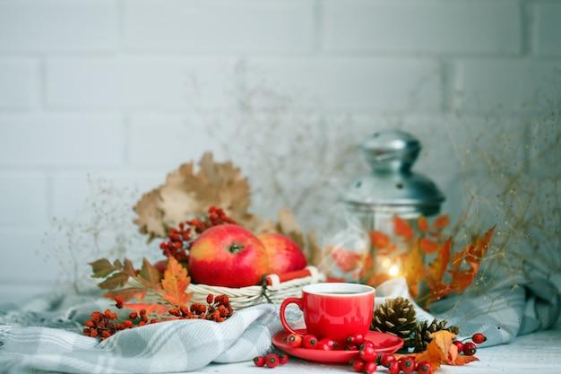 Taza de café, manzanas y hojas de otoño en una mesa de madera.