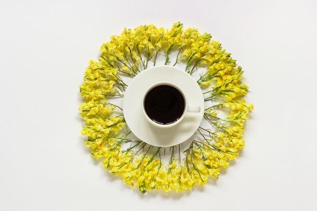 Taza de café y marco circular amarillo flores silvestres sobre fondo gris