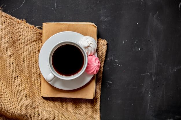 Taza de café, merengue y libro vintage sobre una mesa oscura