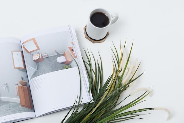 Taza de café en la mesa cerca de un diario y plantas.