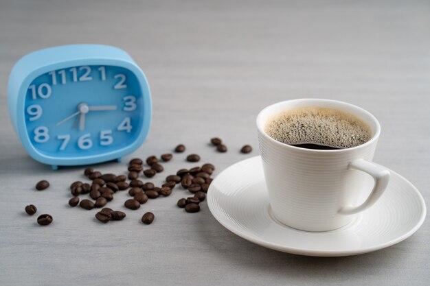 Taza de café en la mesa contra el despertador