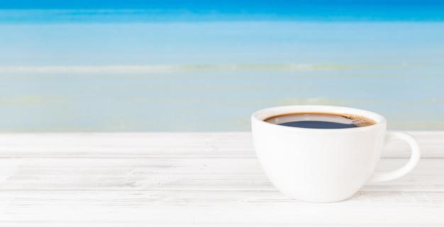 Taza de café en la mesa de madera blanca con fondo de mar azul brillante