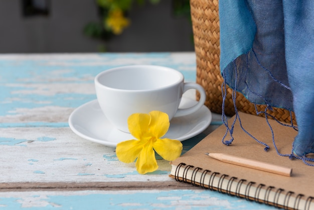 Taza de café en la mesa de madera con cuaderno de notas marrón