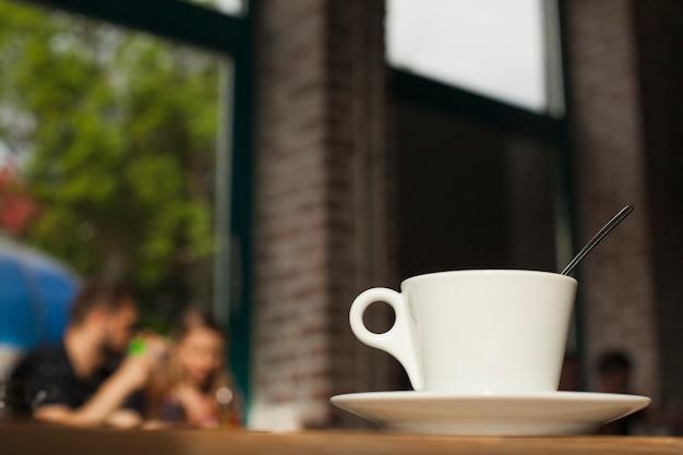 Taza de café en la mesa sobre fondo de cafetería defocused