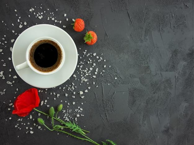 Taza con café en una mesa de textura con flores de amapola y fresas