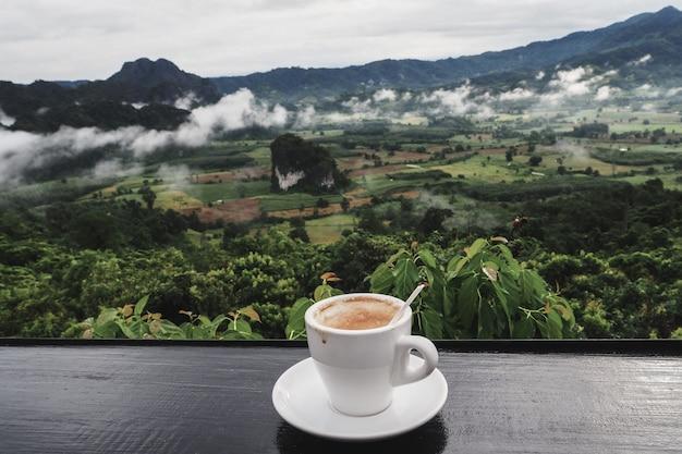 Taza de café en la mesa con vistas a la montaña en la mañana como fondo