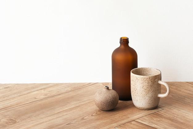 Taza de café mínima por un jarrón marrón sobre un piso de madera
