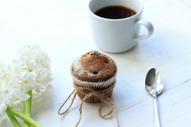 Una taza de café con un muffin y un jacinto sobre fondo blanco