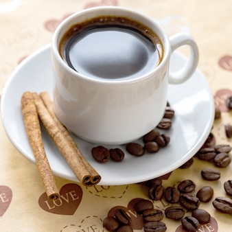 Una taza de café natural en grano y canela.