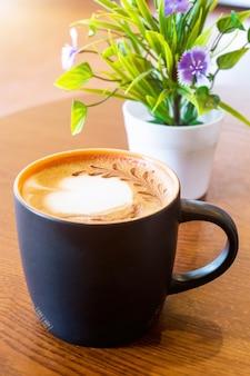 Taza de café negra sobre fondo de mesa de madera marrón. concepto relajante.
