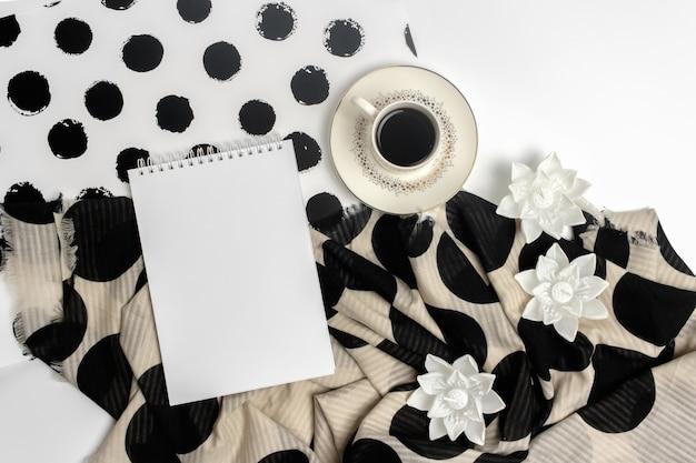 Una taza de café negro, un bloc de notas, velas en forma de flores de loto