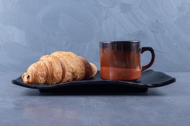 Taza de café negro y croissant para desayunar sobre fondo gris.