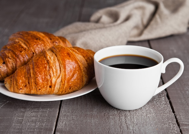 Taza de café negro y croissant para el desayuno en la superficie de madera