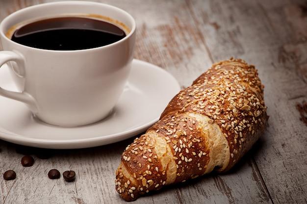 Taza de café negro y croissant sobre madera grunge