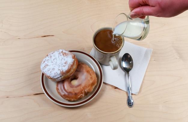 Taza de café negro con donut sobre fondo de madera