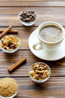 Taza de café negro espresso sobre fondo de madera natural con aperitivos saludables - nueces y pasas