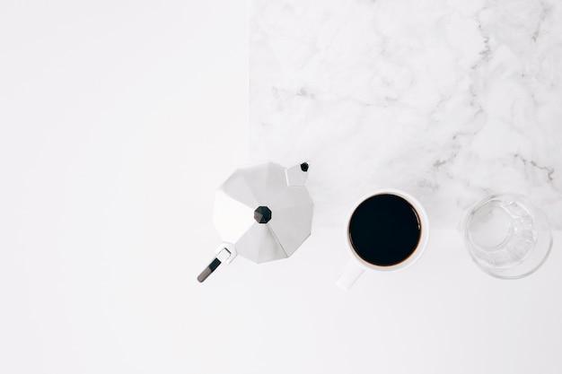 Taza de café negro; fabricante y vaso de agua sobre fondo blanco