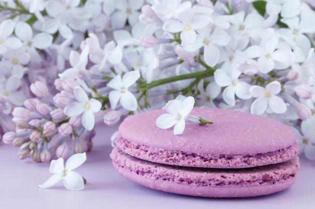 Taza de café negro, flores lilas y dulces macarrones franceses pastel