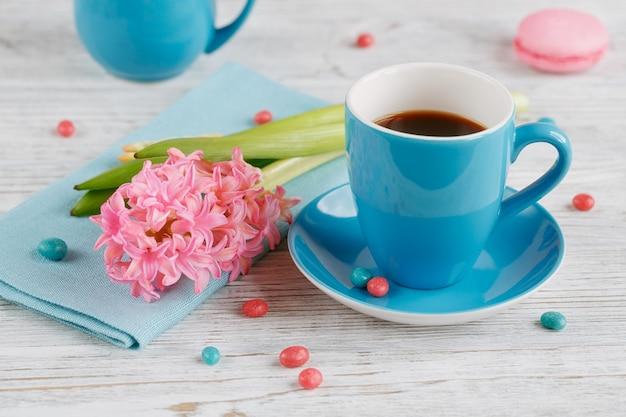 Taza de café negro, flores rosas y macarrones franceses