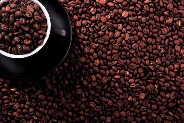 Taza de café negro con fondo de frijoles tostados