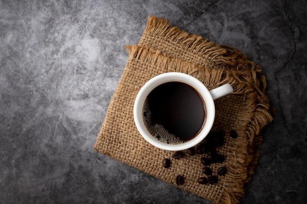 Taza de café negro y granos de café sobre cemento