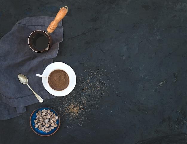 Taza de café negro con higos secos y azúcar de caña sobre piedra oscura, vista superior