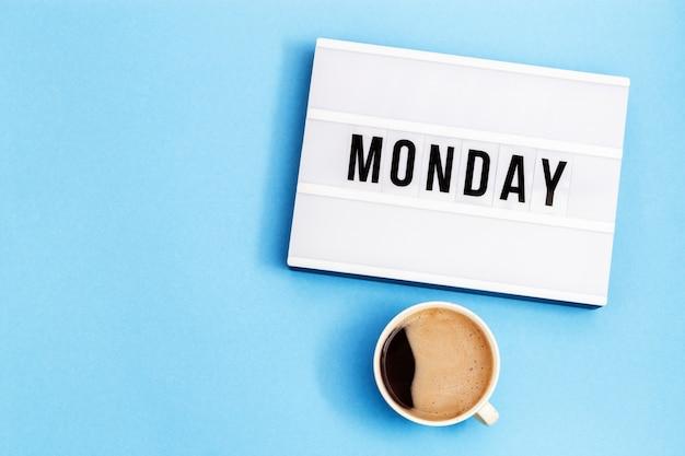Taza de café negro y lightbox con word monday.