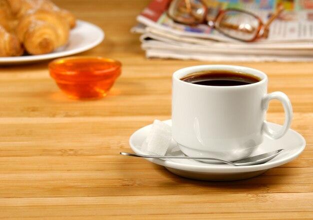 Taza de café negro en la mesa de madera con vasos y periódico a un lado