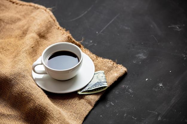 Taza de café negro y pago sobre la mesa