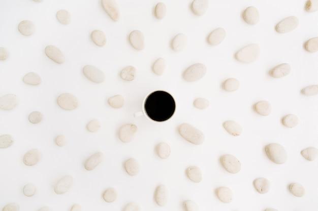 Taza de café negro con patrón neutro de piedras beiges.