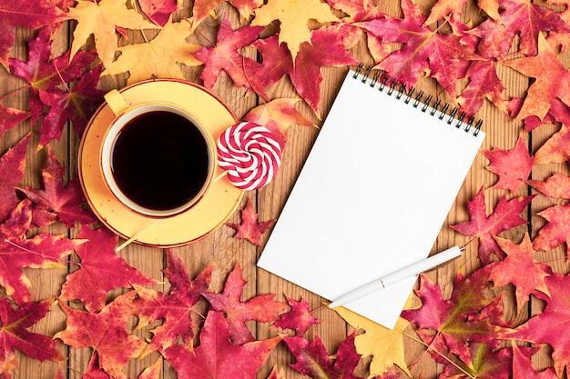 Taza con café negro, piruleta, macarrones, bufanda textil, bloc de notas, mesa de madera con hojas de otoño naranjas caídas lay flat