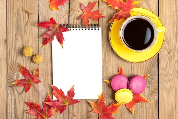 Taza con café negro, piruletas amarillas, macarrones, bloc de notas, mesa de madera con hojas de otoño caídas de naranja lay flat