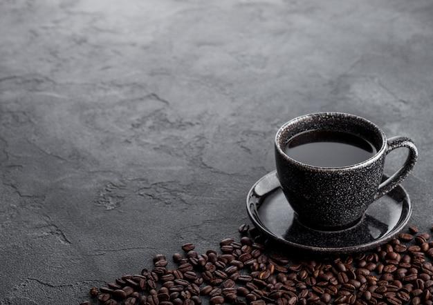 Taza de café negro con platillo y granos de café frescos en la mesa de la cocina de piedra negra.