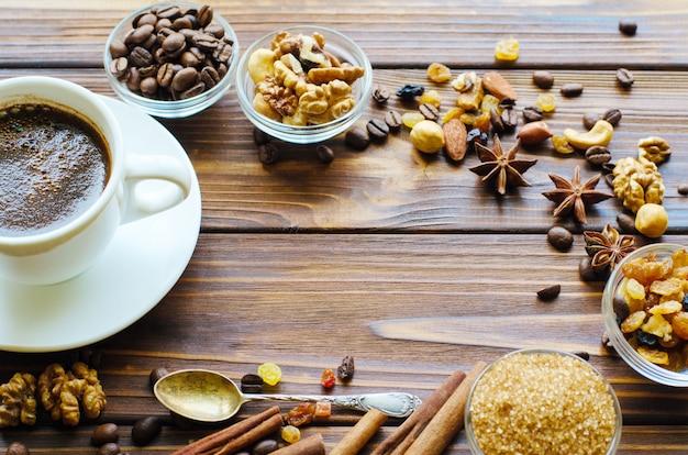 Taza de café negro sobre fondo de madera natural con aperitivos saludables - nueces y pasas. copia espacio en el medio.