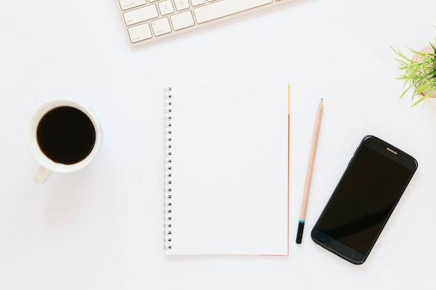 Taza de café con notebook y teléfono