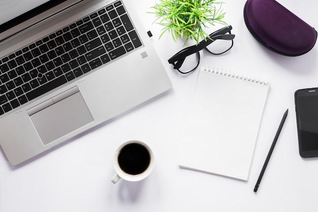 Taza de café; ordenador portátil; los anteojos; bloc de notas de lápiz y espiral con lápiz sobre fondo blanco