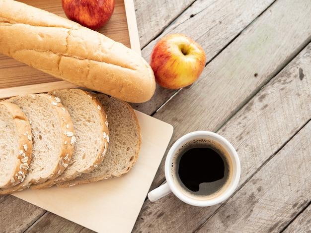 Taza de café y pan de desayuno en la mesa de madera