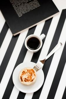 Taza de café y de panadería en fondo blanco y negro rayado.