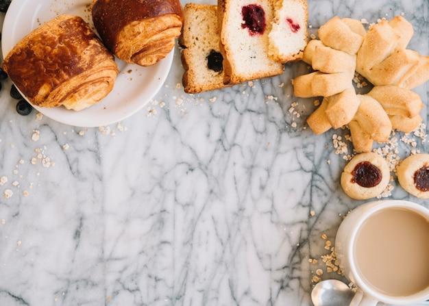Taza de café con panadería en mesa de mármol