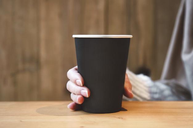 Taza de café de papel artesanal en una mano femenina en una cafetería