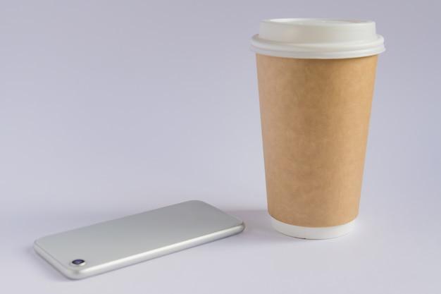 Taza de café de papel artesanal y teléfono inteligente metálico en estilo minimalista
