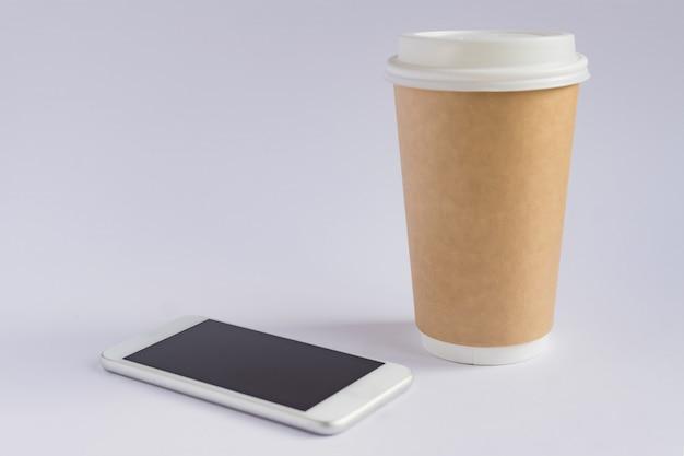 Taza de café de papel artesanal y teléfono inteligente metálico