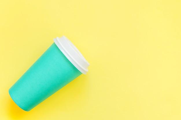 Taza de café de papel azul de diseño laico simplemente aislado sobre fondo de moda colorido amarillo