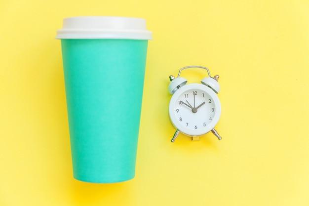 Taza de café de papel azul de diseño plano simplemente laico y reloj despertador aislado en amarillo colorido moderno
