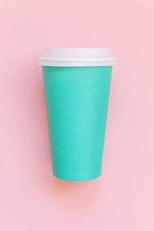 Taza de café de papel azul de diseño simplemente laico plano sobre fondo de moda colorido pastel rosa