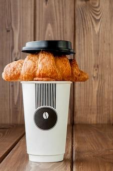 Taza de café de papel y croissant